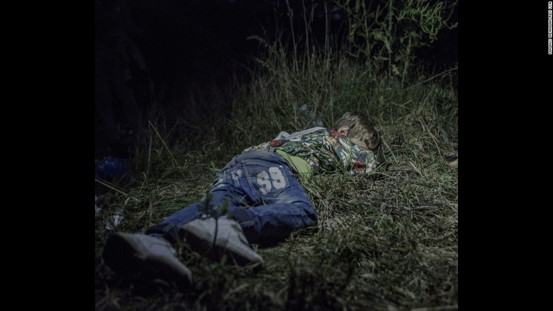 """Ahmed, 6, sleeps on the ground in Horgos, Serbia. The adults were still sitting around after midnight, formulating plans for how they were going to get out of Hungary without registering themselves with the authorities. Ahmed carries his own bag over the long stretches that his family walks by foot. """"He is brave and only cries sometimes in the evenings,"""" says his uncle, who has taken care of him since his father was killed in their hometown in northern Syria."""