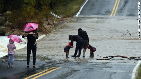 Local residents watch a flooded street in Austin, Texas, on October 24, 2015. Torrential rains created transit mayhem in the US state of Texas on October 24, including a train derailment and scores of canceled flights at one of the nation's busiest airports. AFP PHOTO/JEWEL SAMAD        (Photo credit should read JEWEL SAMAD/AFP/Getty Images)