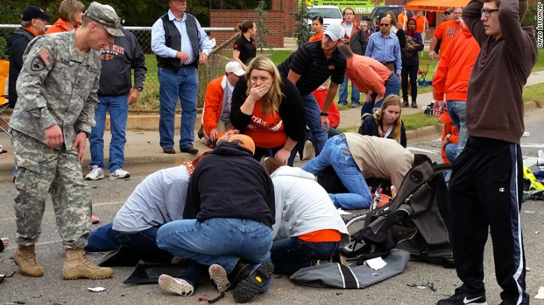 Bystanders help the injured after a vehicle crashed into a crowd of spectators during the Oklahoma State University homecoming parade, causing multiple injuries, on Saturday, Oct. 24, 2015 in Stillwater, Oka.  (David Bitton/The News Press via AP) MANDATORY CREDIT