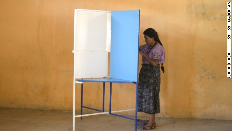 An indigenous woman casts her vote at the Chinautla municipality, 15 km north of Guatemala city,  during Guatemala's run-off election on October 25, 2015. Guatemalans began casting ballots in a presidential run-off Sunday, choosing between a comedian with no political experience and a former first lady, amid the fallout of a massive corruption scandal. AFP PHOTO/ JOHAN ORDONEZ        (Photo credit should read JOHAN ORDONEZ/AFP/Getty Images)