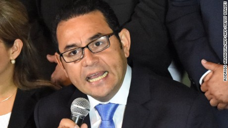 President-elect Jimmy Morales, of the National Front Convergence, delivers a speech next to his wife Hilda Marroquin, after winning the run-off election, in Guatemala City on October 25, 2015. Comedian Jimmy Morales jumped to a massive lead in Guatemala's presidential race Sunday, declaring victory after a campaign upended by a corruption scandal that felled the outgoing president. Morales, a comic actor and TV personality with no political experience, had 69 percent of the vote to 31 percent for former first lady Sandra Torres, with 94 percent of polling stations reporting.   AFP PHOTO / Rodrigo ARANGUA        (Photo credit should read RODRIGO ARANGUA/AFP/Getty Images)