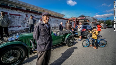 An Aston Martin Le Mans through 1933 is surrounded by curious locals.