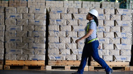 """A worker walks next to packages of corn flour at a distribution center of food company """"Empresas Polar"""" in Maracay, Venezuela on October 27, 2015. Venezuelan businessman Lorenzo Mendoza discarded Tuesday to abandon the country after he was reported by the Chavism before the prosecutor's office for """"betraying his country"""", which could take him to prison for several years. AFP PHOTO / FEDERICO PARRA        (Photo credit should read FEDERICO PARRA/AFP/Getty Images)"""