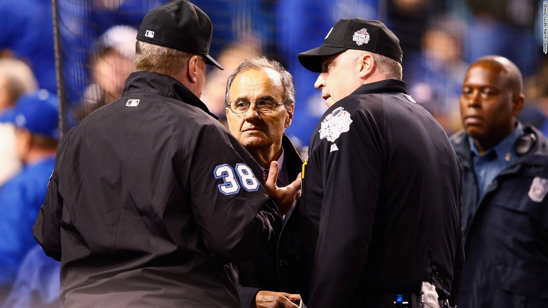 Joe Torre, Major League Baseball's chief baseball officer, meets with umpires in the fourth inning to discuss technical difficulties during Game 1.