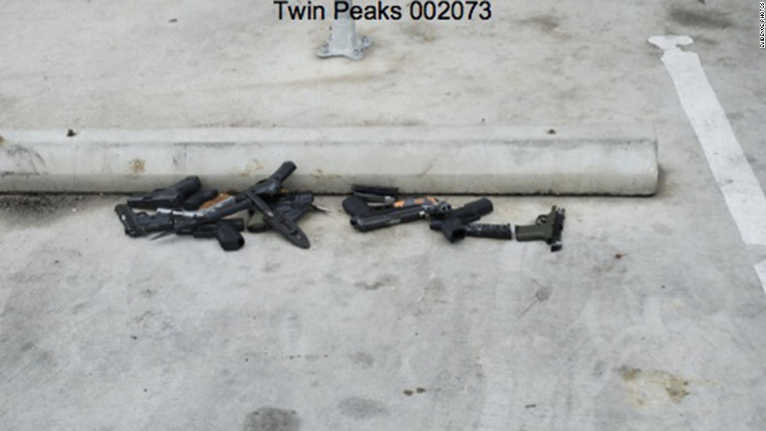 Weapons are piled up by a barrier in the parking lot.