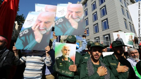 A picture taken on October 11, 2015 shows Iranian men, including members of the Iranian revolutionary guard, holding portraits during the funeral procession of Iran's Revolutionary Guards Brigadier General Hossein Hamedani in Tehran. Many Iranians have died in Syria since early October 2015, a sign of Irans commitment, along with Russia, to support the regime of Syrian President Bashar al-Assad.
