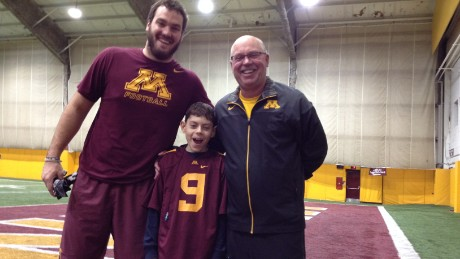 The author's son, Billy Drash, suffers from epilepsy. Here, he poses with Minnesota football coach Jerry Kill and tight end Drew Goodger. The meeting was a turning point in the boy's care.