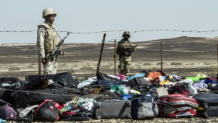 Egyptian army soldiers stand guard next to the luggage and belongings of passengers of the A321 Russian airliner piled up at the site of the crash in Wadi el-Zolmat, a mountainous area in Egypt's Sinai Peninsula on Sunday, November 1. International investigators began probing why a Russian airliner carrying 224 people crashed in Egypt's Sinai Peninsula, killing everyone on board, as rescue workers widened their search for missing victims.