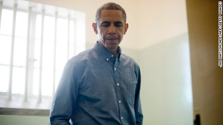 US President Barack Obama visits the cell where Nelson Mandela, an anti-apartheid activist, was once jailed on Robben Island, on June 30, 2013. Paying homage to the 94-year-old former South-African president, who is critically ill in hospital, Obama stared into the stark cell where Mandela spent two thirds of his 27 years in jail.  AFP PHOTO/JIM  WATSON        (Photo credit should read JIM WATSON/AFP/Getty Images)