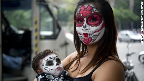 "A woman painted as ""Catrina"" poses for pictures at the Angel of Independence square before taking part in the Procession of the Catrinas along Reforma Avenue in Mexico City on October 25, 2015. Catrina is a cartoon character created by cartoonist Jose Guadalupe Posada and baptized by artist Diego Rivera, who popularized it and whose character is now part of Mexican culture during the celebrations of the Day of the Dead.   AFP PHOTO / Yuri CORTEZ        (Photo credit should read YURI CORTEZ/AFP/Getty Images)"