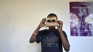 A man with a cardboard Virtual Reality headset. Cheap materials could make VR accessible to a mass market.