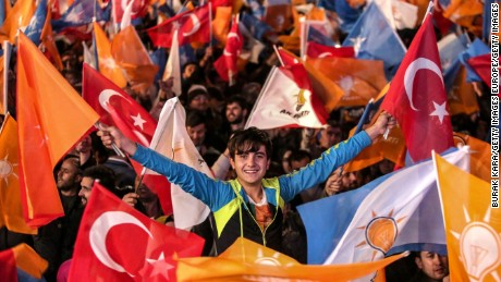 ANKARA, TURKEY - NOVEMBER 01:  People wave flags outside the ruling AK Party headquarters on November 1, 2015, in Ankara, Turkey. Polls have opened in Turkey's second general election this year, with the ruling Justice and Development Party (AKP) hoping to win a majority, as the country searches for stability amongst serious security concerns. (Photo by Burak Kara/Getty Images)
