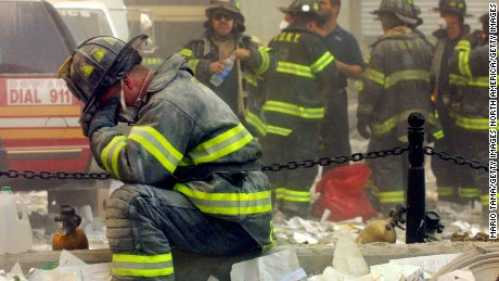 A firefighter breaks down after the World Trade Center buildings collapsed September 11, 2001 after two hijacked airplanes slammed into the twin towers in a terrorist attack. (Photo by Mario Tama/Getty Images)