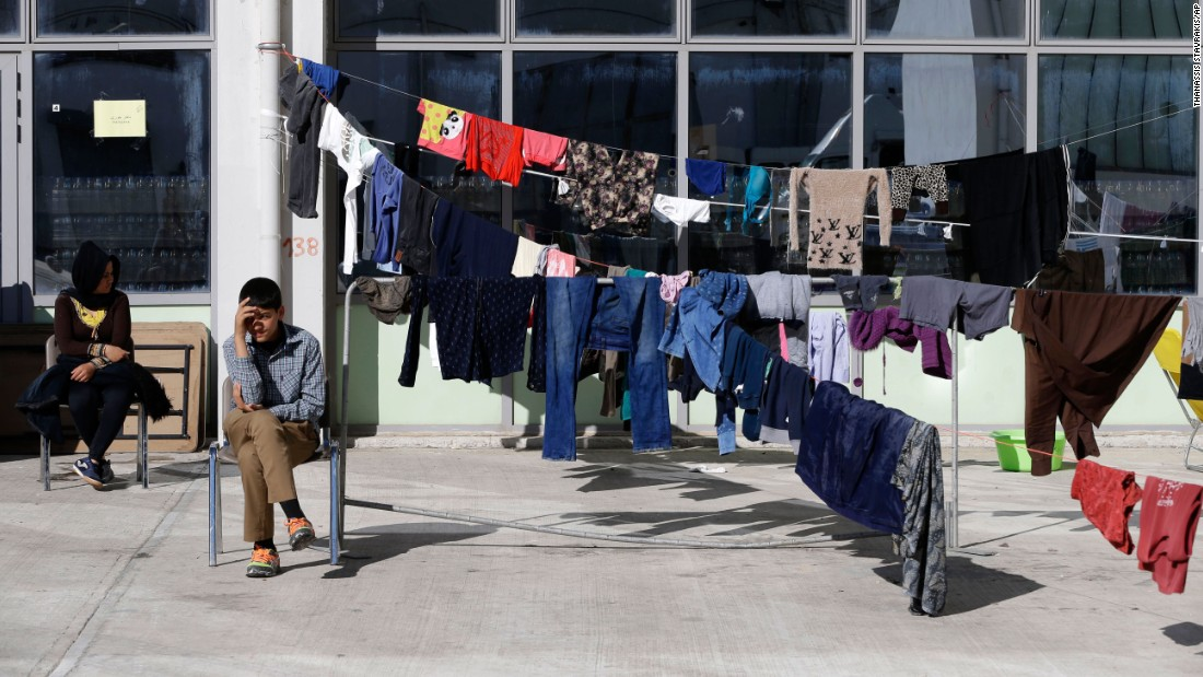 Afghan migrants sit next to drying laundry at the Galatsi Olympic Hall in Athens, Greece, on Wednesday, November 4.
