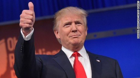 Real estate tycoon Donald Trump flashes the thumbs-up as he arrives on stage for the start of the prime time Republican presidential debate on August 6, 2015 at the Quicken Loans Arena in Cleveland, Ohio. AFP PHOTO/MANDEL NGAN        (Photo credit should read MANDEL NGAN/AFP/Getty Images)
