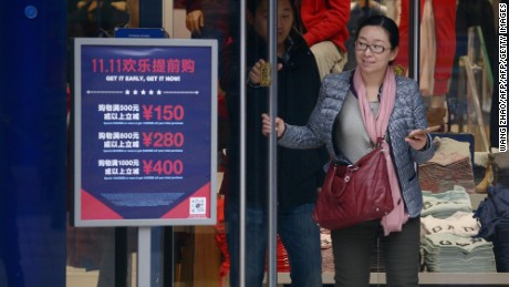 "A woman walks out a shop past a ""Singles Day"" sales promotional board in Beijing on November 11, 2015.  Shoppers spent around 9 billion USD in the first 12 hours of China's ""Singles Day"" sale on November 11, e-commerce giant Alibaba said, in the world's biggest online shopping day.         AFP PHOTO / WANG ZHAO        (Photo credit should read WANG ZHAO/AFP/Getty Images)"