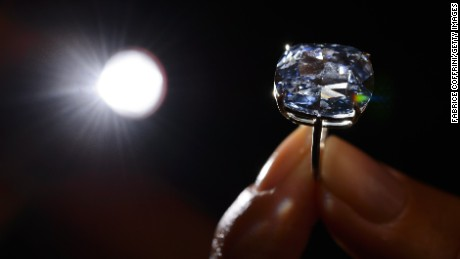 A model holds a 12.03-carat blue diamond during a press preview by auction house Sotheby's in Geneva on November 4, 2015. A 12.03-carat blue diamond could fetch a record $55 million (47 million Euros) when it goes under the hammer by Sotheby's on November 11 in Geneva. Categorised as a fancy vivid blue diamond, the Blue Moon, discovered in South Africa in January last year, is the largest cushion-shaped stone in that category to ever appear at auction.  AFP PHOTO / FABRICE COFFRINI        (Photo credit should read FABRICE COFFRINI/AFP/Getty Images)