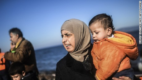 A woman holds her child as refugees and migrants get off a dinghy upon their arrival on the Greek island of Lesbos after crossing the Aegean Sea from Turkey on November 12, 2015. EU leaders attending a summit with their African counterparts approved a 1.8-billion-euro trust fund for Africa aimed at tackling the root causes of mass migration to Europe. AFP PHOTO / BULENT KILIC        (Photo credit should read BULENT KILIC/AFP/Getty Images)