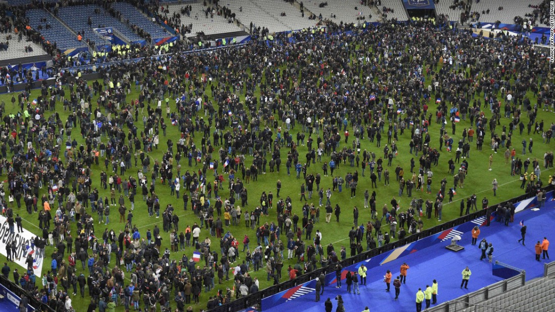 Spectators gather on the field of the Stade de France following the attacks. Explosions were heard during the soccer match between France and Germany.