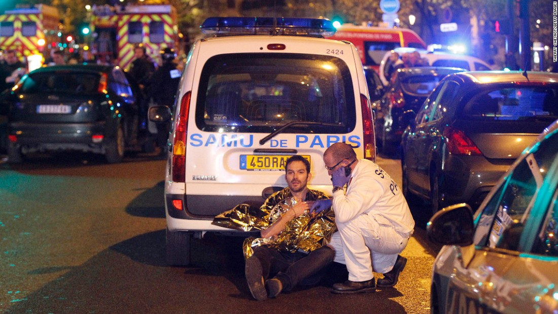 A medic tends to a wounded man following the attacks near the Boulevard des Filles du Calvaire.