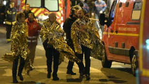 Security forces evacuate people on Rue Oberkampf near the Bataclan concert hall in central Paris early on November 14, following a string of terror attacks across Paris that began Friday night. There were also explosions at the Stade de France, just north of Paris.