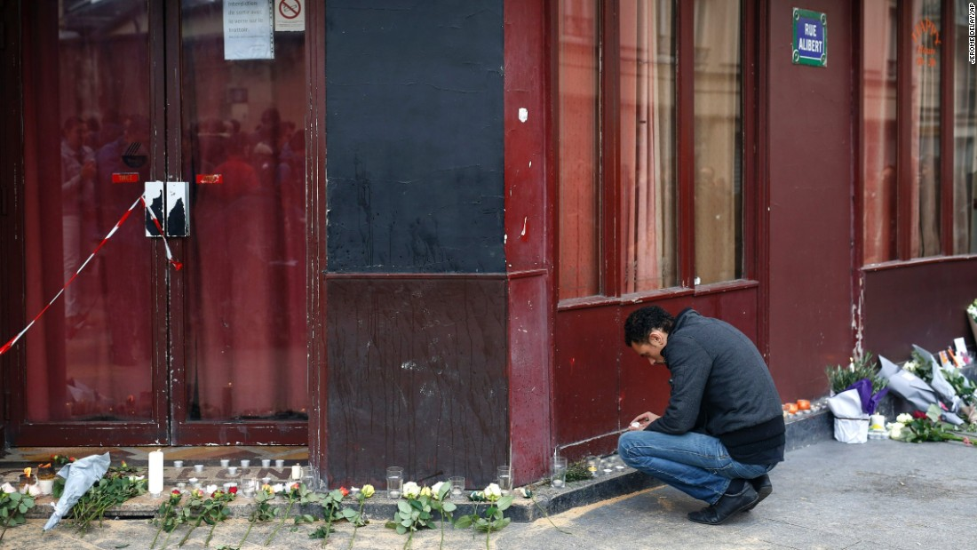 A man places a candle in front of Le Carillon cafe in Paris on November 14.