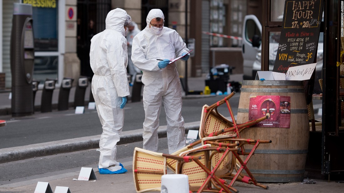 A forensic scientist works near a Paris cafe on Saturday, November 14, following a series of coordinated attacks in Paris the night before that killed scores of people. ISIS has claimed responsibility.