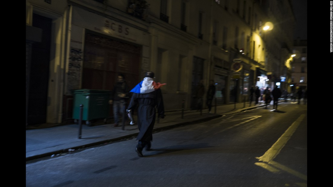 'A man wearing a French flag walks through the streets of Paris on November 14. French President Francois Hollande has declared a state of emergency.' from the web at 'http://i2.cdn.turner.com/cnnnext/dam/assets/151114202206-03-paris-aftermath-super-169.jpg'