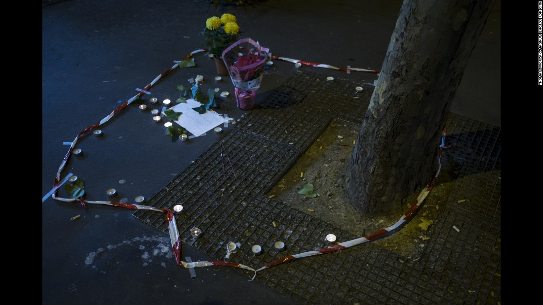 'Candles and flowers are seen on November 14 at the spot where a victim died on the Rue de la Fontaine au Roi. Five people were killed in a shooting outside a bar in Paris' 11th district, according to prosecutor Francois Molins.' from the web at 'http://i2.cdn.turner.com/cnnnext/dam/assets/151114202218-04-paris-aftermath-super-169.jpg'