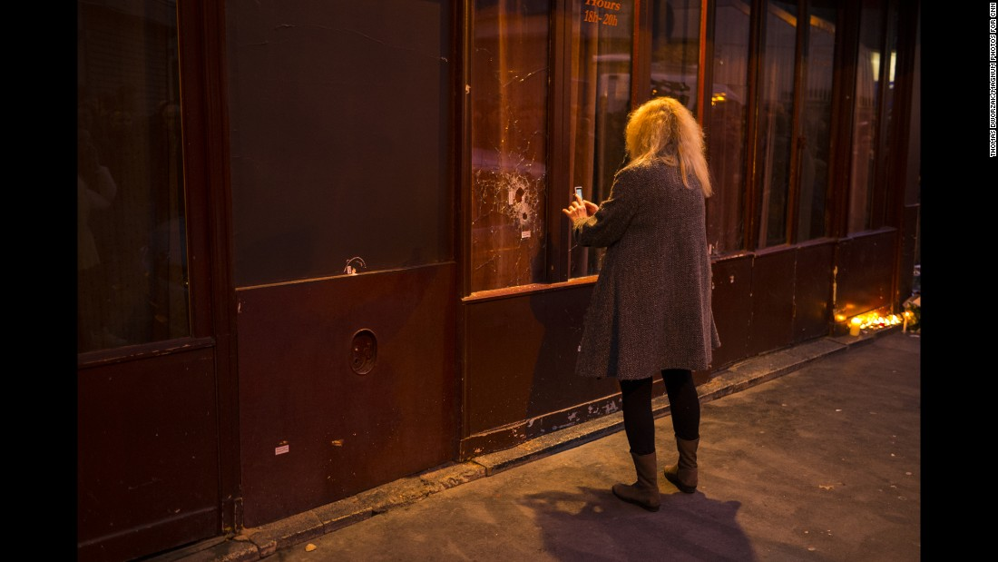 'A woman takes a picture of a window shattered by bullets on November 14.' from the web at 'http://i2.cdn.turner.com/cnnnext/dam/assets/151114202229-05-paris-aftermath-super-169.jpg'