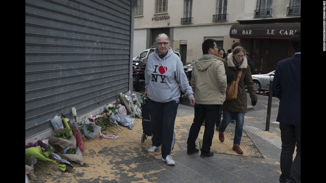 'A woman walks past a memorial in Paris' 10th district November 14.' from the web at 'http://i2.cdn.turner.com/cnnnext/dam/assets/151114202302-08-paris-aftermath-super-169.jpg'