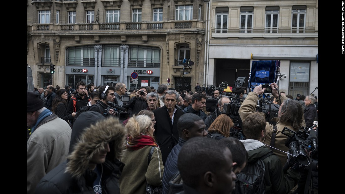 'Bernard-Henri Levy, a prominent French philosopher, stands in the center of a crowd near the Bataclan on November 14.' from the web at 'http://i2.cdn.turner.com/cnnnext/dam/assets/151114202312-09-paris-aftermath-super-169.jpg'