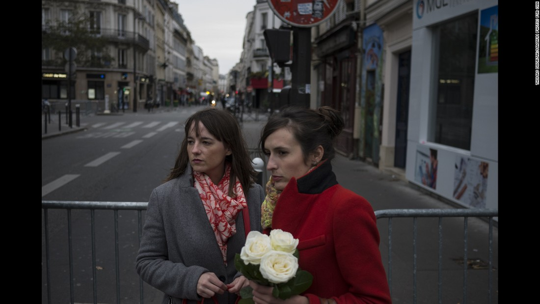 'Women pay their respects near the Bataclan on November 14. Three gunmen shot concertgoers and held hostages late Friday night until police raided the building.' from the web at 'http://i2.cdn.turner.com/cnnnext/dam/assets/151114202322-10-paris-aftermath-super-169.jpg'