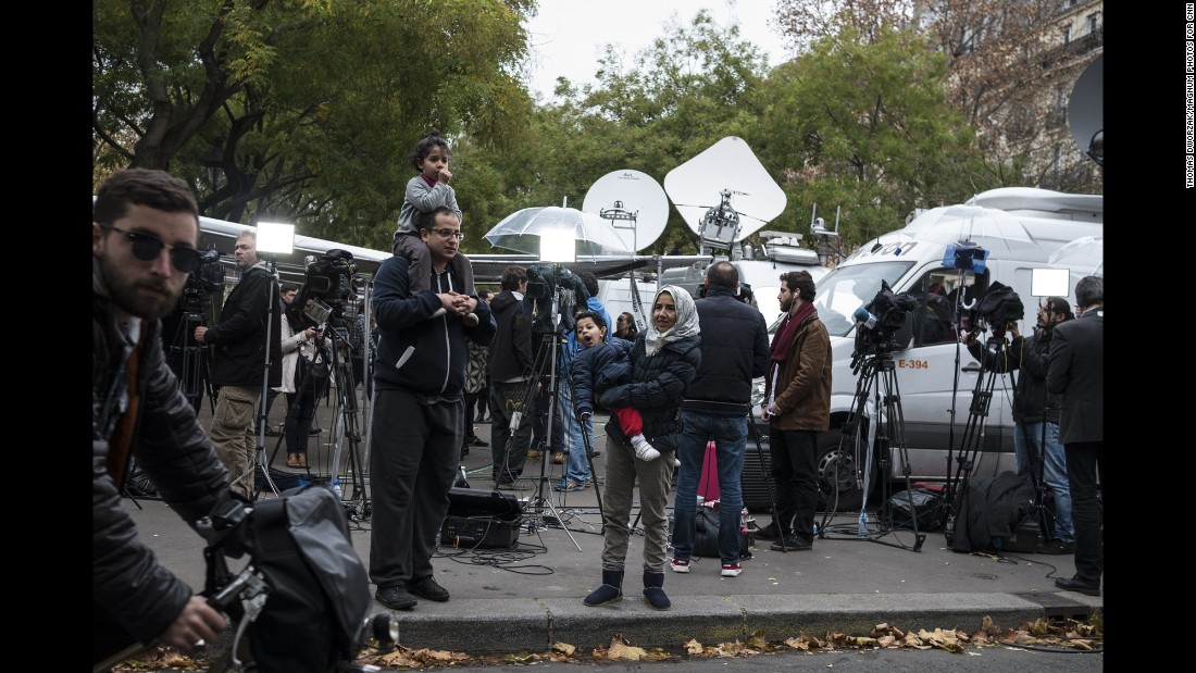 'A family stands among TV crews set up on November 14 near the Bataclan.' from the web at 'http://i2.cdn.turner.com/cnnnext/dam/assets/151114202344-12-paris-aftermath-super-169.jpg'