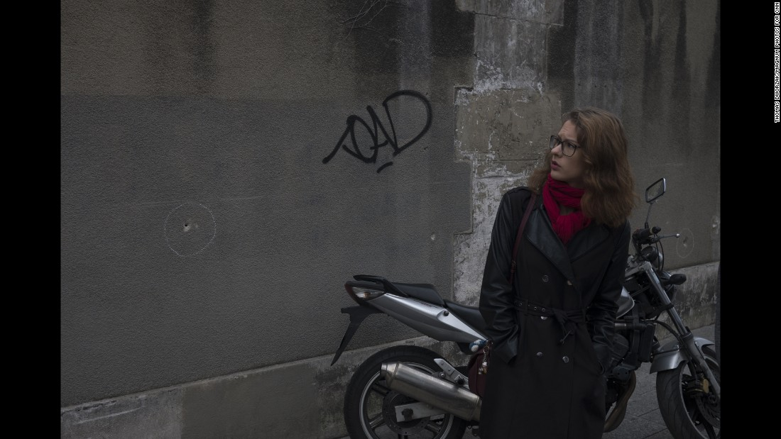 'A woman observes bullet holes in a wall near the Paris restaurant Le Petit Cambodge on Saturday, November 14.' from the web at 'http://i2.cdn.turner.com/cnnnext/dam/assets/151114202456-01-paris-aftermath-super-169.jpg'