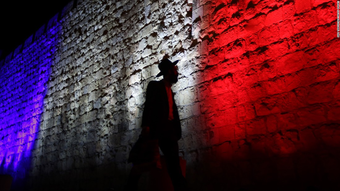 A man walks past Jerusalem's Old City walls, which were illuminated in the colors of the French flag on November 15.