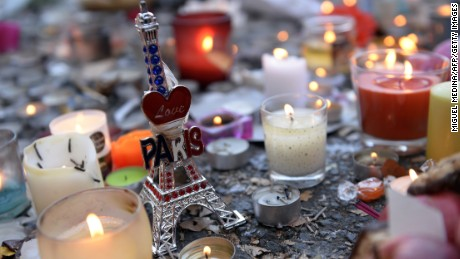 Candles and a small statue of the Eiffel Tower are placed at a memorial along a police cordon set-up close to the Bataclan concert hall on November 15, 2015, two days after a series of deadly attacks. Islamic State jihadists claimed a series of coordinated attacks by gunmen and suicide bombers in Paris on November 13 that killed at least 128 people in scenes of carnage at a concert hall, restaurants and the national stadium. AFP PHOTO / MIGUEL MEDINA        (Photo credit should read MIGUEL MEDINA/AFP/Getty Images)