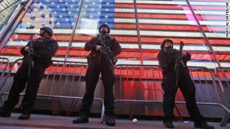 """Heavily armed New York city police officers with the Strategic Response Group stand guard at the armed forces recruiting center in New York's Times Square, Saturday, Nov. 14, 2015.  Police in New York say they've deployed extra units to crowded areas of the city """"out of an abundance of caution"""" in the wake of the attacks in Paris, France. A New York Police Department statement released Friday stressed police have """"no indication that the attack has any nexus to New York City."""" (AP Photo/Mary Altaffer)"""