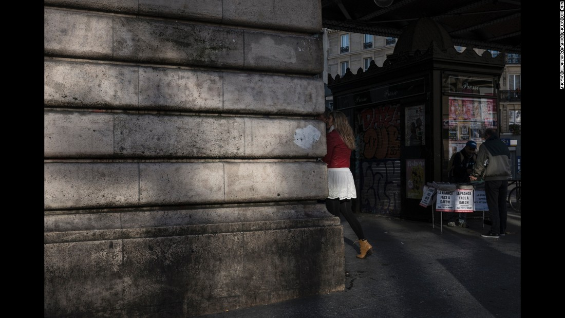 'People walk past a man selling newspapers near the Barbes-Rochechouart Metro station on November 15.' from the web at 'http://i2.cdn.turner.com/cnnnext/dam/assets/151115204914-02-paris-aftermath-1115-super-169.jpg'
