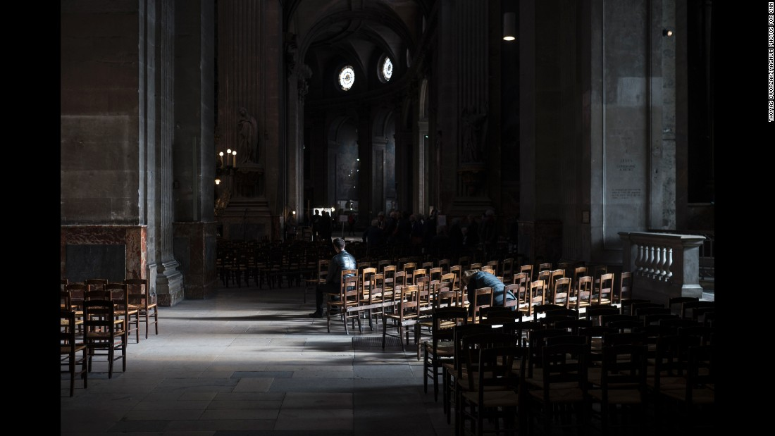 'People sit inside the St. Sulpice Catholic church on November 15 in Paris.' from the web at 'http://i2.cdn.turner.com/cnnnext/dam/assets/151115204936-04-paris-aftermath-1115-super-169.jpg'