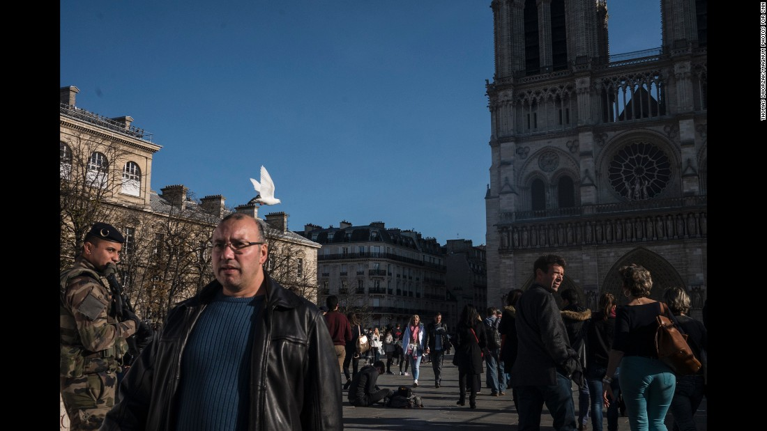 'Tourists walk past Notre Dame on November 15 as the military and police patrol the area.' from the web at 'http://i2.cdn.turner.com/cnnnext/dam/assets/151115204959-06-paris-aftermath-1115-super-169.jpg'