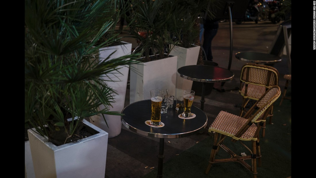 'Drinks sit abandoned on a cafe terrace near Place de la République after a false alarm caused a panic on November 15.' from the web at 'http://i2.cdn.turner.com/cnnnext/dam/assets/151115205104-12-paris-aftermath-1115-super-169.jpg'