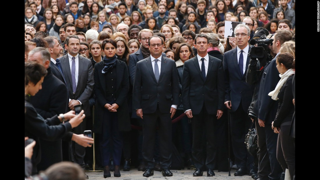 French President Francois Hollande, center, flanked by French Prime Minister Manuel Valls, right, and French Education Minister Najat Vallaud-Belkacem, center left, stands among students during a minute of silence in the courtyard of the Sorbonne University in Paris on November 16.