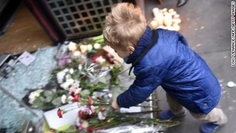 A boy lays flowers outside a Japanese restaurant next to the cafe 'La Belle Equipe', Rue de Charonne, in Paris on November 14.