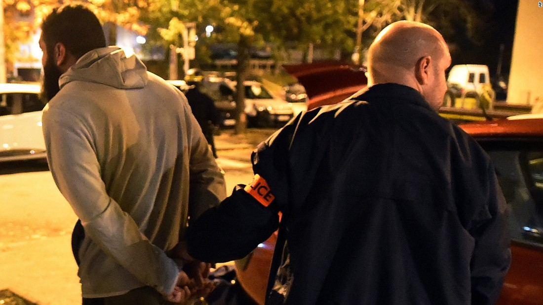 A man is detained by a police officer after a raid in the Mirail district of Toulouse, France, on November 16. French Prime Minister Manuel Valls said there were 150 police raids overnight in the country.