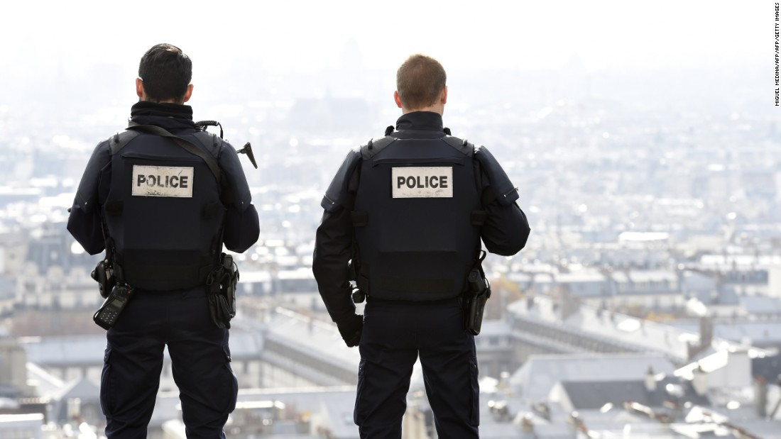Police officers overlook Paris as they patrol in front of the Sacre Coeur Basilica on November 16.