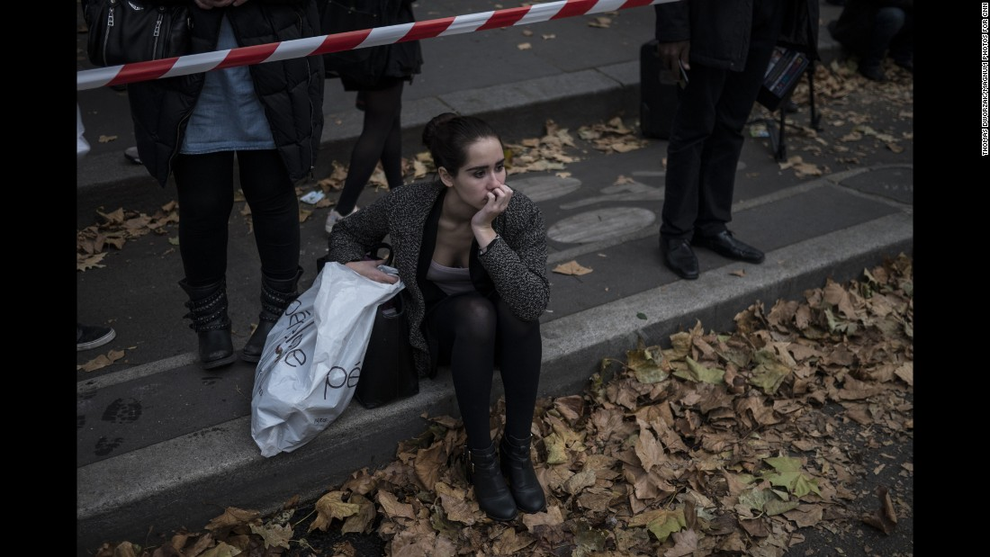 'A woman on November 16 sits in front of the Parisian concert venue Balaclan, where many of the victims from the Paris attacks were killed.' from the web at 'http://i2.cdn.turner.com/cnnnext/dam/assets/151116203633-02-paris-aftermath-1116-super-169.jpg'