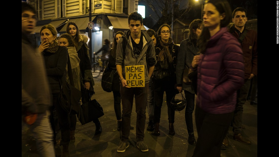 "'A young man in Paris on November 16 holds a sign that reads ""Not even afraid"" in the neighborhood of Le petit Cambodge, a restaurant that was hit in the attacks.' from the web at 'http://i2.cdn.turner.com/cnnnext/dam/assets/151116210932-04-paris-aftermath-1116-super-169.jpg'"