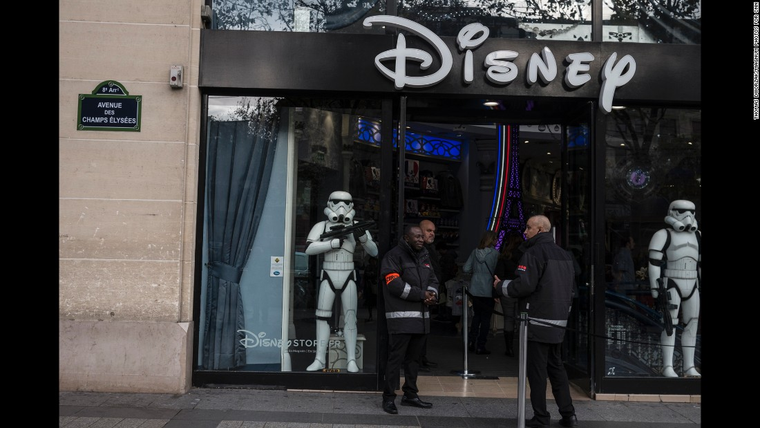 'Security guards stand outside a Disney store on Champs Elysees in Paris on November 16.' from the web at 'http://i2.cdn.turner.com/cnnnext/dam/assets/151116211205-05-paris-aftermath-1116-super-169.jpg'
