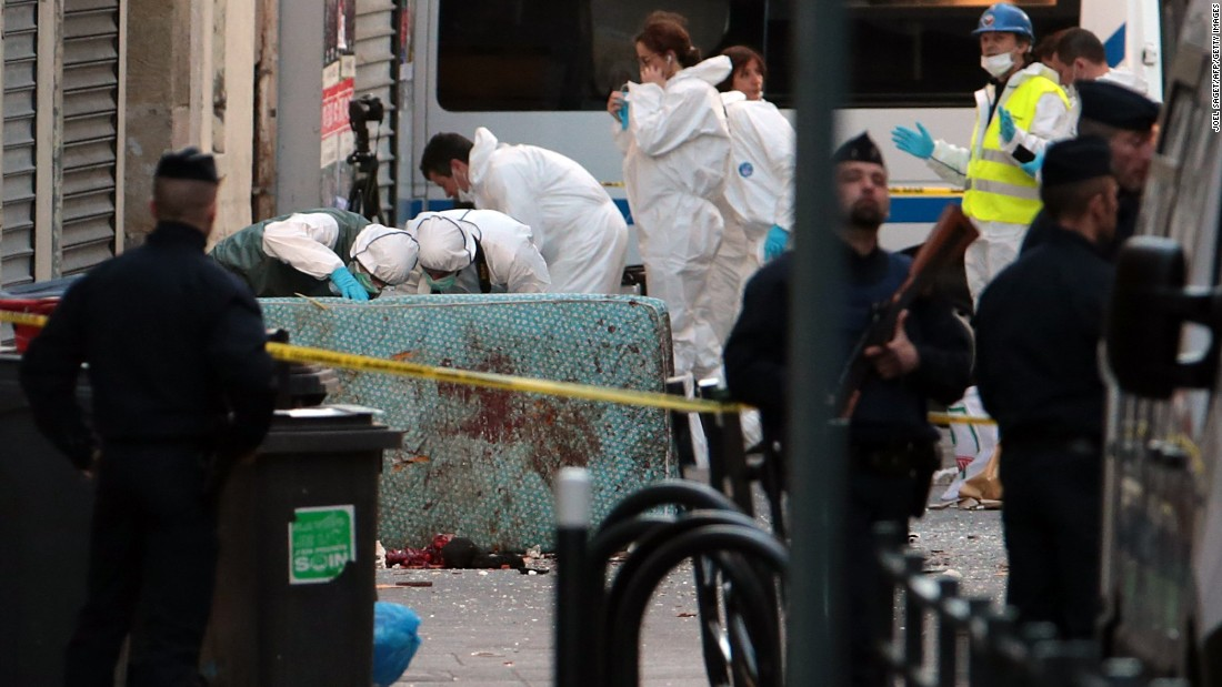 A forensics team searches for evidence outside the building on November 18.